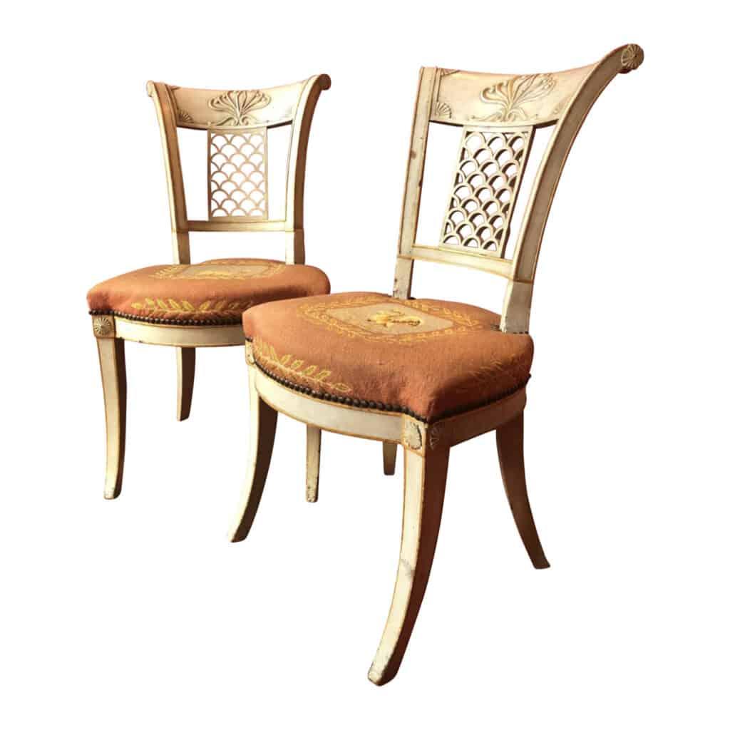 Paire de chaises à dossiers évasés enroulés, en hêtre laqué, mouluré et sculpté, reposant sur des pieds  en sabre, style Directoire.
