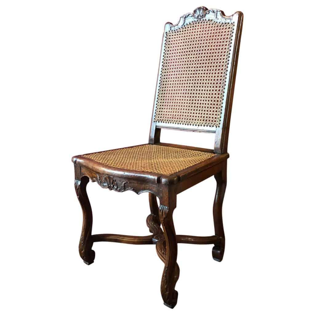 Chaise cannée, en hêtre mouluré et sculpté, pieds en forme d'os de mouton. Époque fin Louis XIV, début Régence. En vente sur Antikeo.